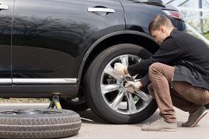 Bild Mann wechselt die Reifen