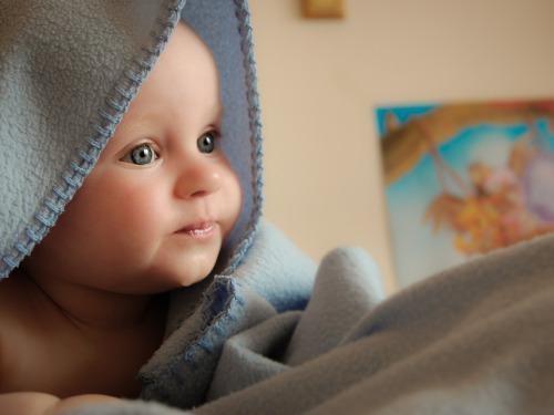 Baby mit einer Decke auf dem Kopf