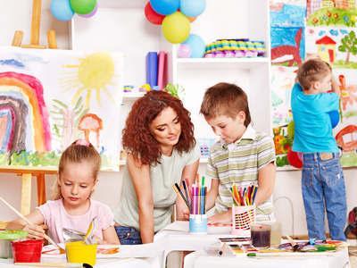Tagesmutter mit Kindern beim Malen