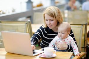 Mutter arbeitet mit Baby auf dem Schoß