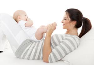 Baby sitzt auf Bauch der Mutter
