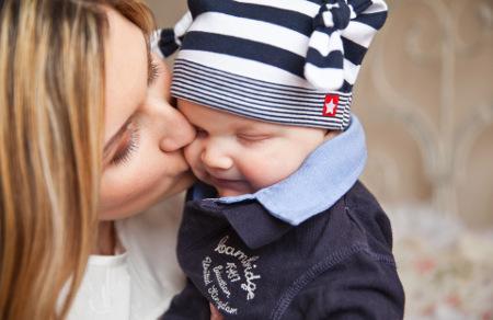 Mutter küsst Kind auf Backe