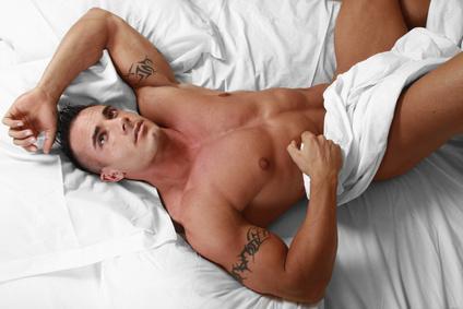 nackter Mann auf einem Bett