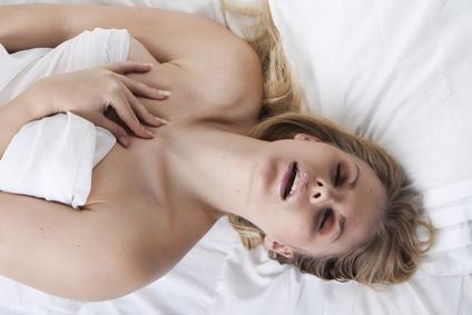 Frau genießt eine Yoni-Massage im Bett