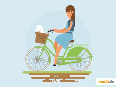 Fahrradfahrerin mit Hund im Korb / Radtour mit Hund