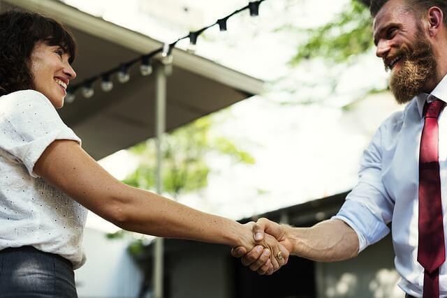 Zwei Menschen geben sich einen Handschlag