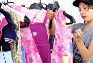Bild Kind sieht auf Flohmarkt nach Kleidung