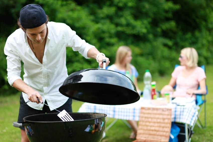 Bild Mann beim Grillen mit Holzkohlegrill