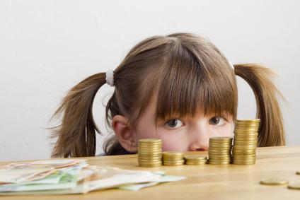 Kind schaut auf viele Geldscheine und Münzen.