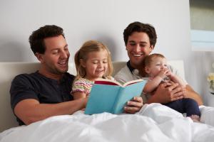 Adoptiveltern lesen Kindern eine Geschichte vor