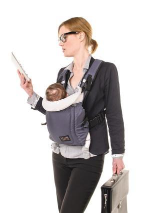 Mama arbeitet mit Baby in Tragetasche
