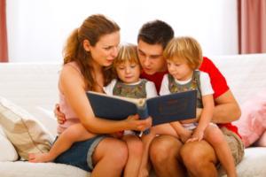 Eltern lesen beiden Kindern etwas vor