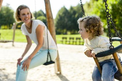 Bild von Babysitter mit Kind auf dem Spielplatz