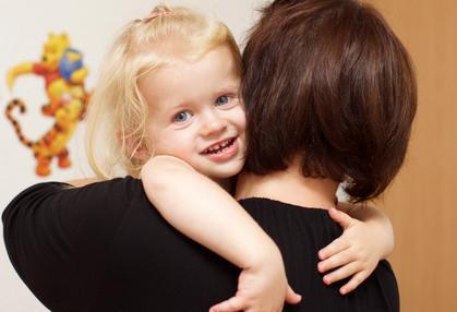 Tagesmutter beim Tragen eines Kindes