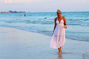 Frau in weißem Strandkleid