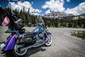 Bild blaues Motorrad vor bergiger Landschaft