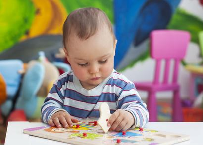 Kind sitzt an Tisch und spielt mit Spielsteinen
