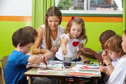 Betreuerin sitzt mit mehreren Kindern an einem Tisch und spielt