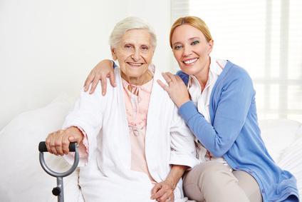 Pflegerin sitz neben Frau auf dem Bett