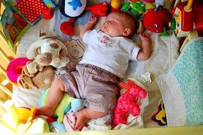 Bild Baby umringt von Spielzeug