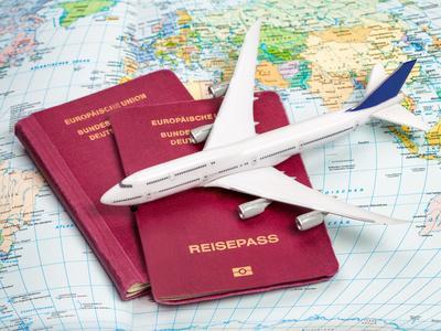 Bild Reisepässe und Flugzeug auf einer Weltkarte