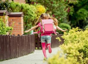 Bild Kind rennt mit Schulranzen zur Schule