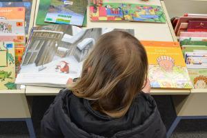 Bild Mädchen liest in Bibliothek